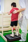 stock photo of infirmary  - physician supports a child standing on the training platform - JPG