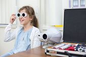 stock photo of infirmary  - girl in red and green glasses at ophthalmologist - JPG