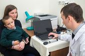stock photo of lap  - boy sits in mothers lap at medical check in front of a doctor - JPG