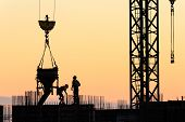 stock photo of concrete pouring  - Builders poured concrete in a new building at sunset - JPG