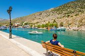 picture of greek-island  - Young lady in blue sitting on bench on wharf of small fishermens - JPG