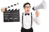 stock photo of beret  - Young movie director with a black beret holding a clapperboard and speaking on a megaphone isolated on white background - JPG