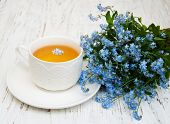 foto of forget me not  - Cup of tea and forget me not flowers on a wooden background - JPG