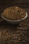 foto of cumin  - Cumin seeds against wooden background - JPG
