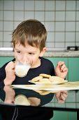 image of milk  - cheerful little boy drinking milk sitting at the dinner table - JPG