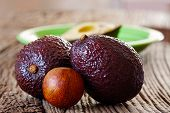 stock photo of avocado  - Two ripe avocados and avocado core on an old rustic wooden plank - JPG