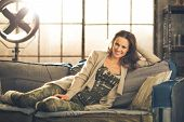 foto of legs apart  - A brunette woman is smiling relaxing on a sofa feet curled under her wearing comfortable clothing leggings and a cardigan - JPG
