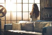 image of comfort  - Looking away a brunette woman in comfortable clothing is standing in a loft living room hugging herself looking out the window - JPG