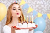 stock photo of dress-making  - Portrait of a young beautiful blond girl wearing cone cap holding a red plate with birthday cake and blowing candles making a wish - JPG