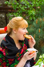 picture of cheeky  - Cheeky Russian cheerful young woman with a scarf draped pavloposadskie and drinking tea with bagel - JPG