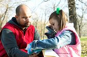 foto of father daughter  - little pretty child and father reading the book in the park - JPG