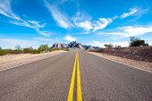 picture of superstition mountains  - A remote and deserted desert road with a beautiful sky - JPG