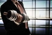 successful business man holding a heavy dumbbell. the concept of success in a hard work of business. poster
