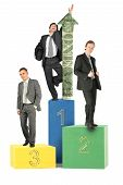 Three Businesmen On Wood Toy Blocks Victory Podium With Dollar Arrow Collage