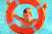 Cheerful Little Boy Looks Through Red Buoy From The Swimming-pool