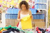 Young Woman In Store Holding Yellow Shirt And Looking On It, Other Commodity, Shallow Depth Of Focus