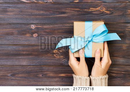 poster of Woman hands give wrapped valentine or other holiday handmade present in paper with red blue and green ribbon. Present box decoration of gift on white wooden table top view with copy space.