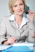 Woman holding headset.