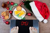 Female Feet On Digital Scales With Sign omg! Surrounded By Christmas Decorations, Bottle, Glass Of poster