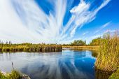 Indian summer in Canada. Magic reflection. Cirrus clouds are reflected in the Winnipeg River, Old Pi poster