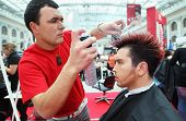 MOSCOW - OCTOBER 2: Hairdresser with hair spray makes hairstyle for man at XVII International Festival