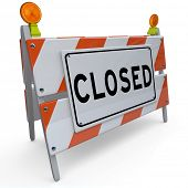 A construction barricade with the word Closed, signifying that a road or street is closed off for ac