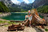 Happy traveler on a Hinterer Gosausee (Upper Gosau Lake) against Dachstein peak. Gosau, Salzkammergut, Austria, Europe.