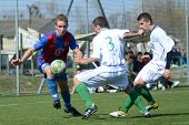KAPOSVAR, HUNGARY - MARCH 17: Tamas Dobos (C) in action at the Hungarian National Championship under 18 game between Kaposvar(white)  and Videoton (blue) March 17, 2012 in Kaposvar, Hungary.