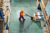 stock photo of lift truck  - worker with fork pallet truck stacker in warehouse loading furniture panels - JPG