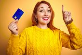 Young customer redhead woman holding credit card over yellow isolated background surprised with an i poster