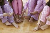 Lower section of four girls painting their toenails