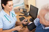 British nurse taking senior man's blood pressure
