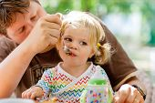 Young Middle-aged Father Feeding Cute Little Toddler Girl In Restaurant. Adorable Baby Child Learnin poster