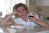 picture of alcohol abuse  - mature addictet woman drinking wine and pills - JPG