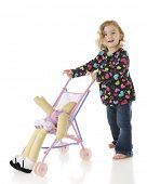 An adorable preschooler pushing her doll yin an umbrella stroller, but the doll is slipping out.  On