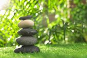 Stack Of Stones On Green Grass Against Blurred Background, Space For Text. Zen Concept poster