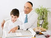 stock photo of matzah  - father and son celebrating passover reading the Hagada - JPG