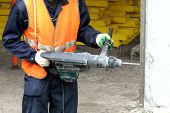Worker hammer drill a hole in the concrete.