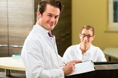 Doctor or dentist with white coat and receptionist standing in a he gives her a clipboard