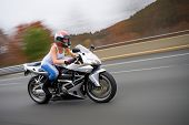 image of crotch-rocket  - A pretty blonde girl in action driving a motorcycle at highway speeds - JPG