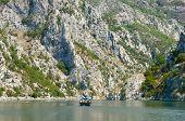 small boat between steep cliffs of Koman-Fierza Lake