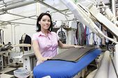 Portrait of a happy young woman standing by ironing machine in laundry