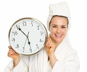 Happy Young Woman In Bathrobe Holding Clock