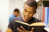 male african university student reading in library