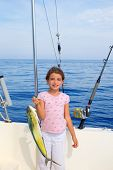 stock photo of mahi  - child girl fishing in boat with mahi mahi dorado fish catch with rod and trolling reels - JPG