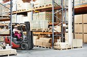 stock photo of forklift driver  - warehouse worker driver in uniform loading cardboxes by forklift stacker loader - JPG