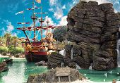 stock photo of pirate flag  - Pirate ship in the backwater of tropical pirate island with big rock in form of skull near it - JPG