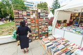 SARAJEVO, BOSNIA - AUGUST 11: Woman perusing bookshelves on street market on August 11, 2012 in Sara