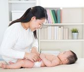 Asian mother changing diaper to baby girl at home.