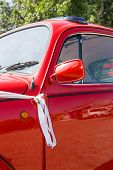 stock photo of beetle car  - Details of a red and shiny vintage beetle car - JPG